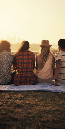 Friends sitting on blanket during sunset