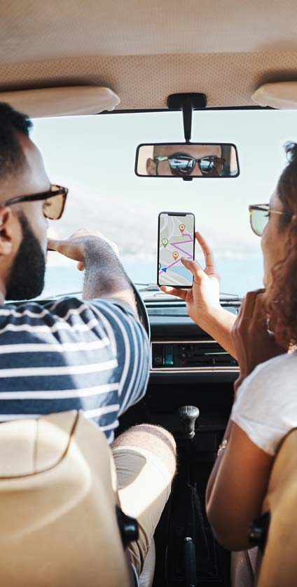 Couple in car looking at cell phone map directions