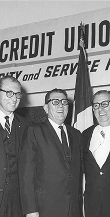 Three men standing near a flag with glasses