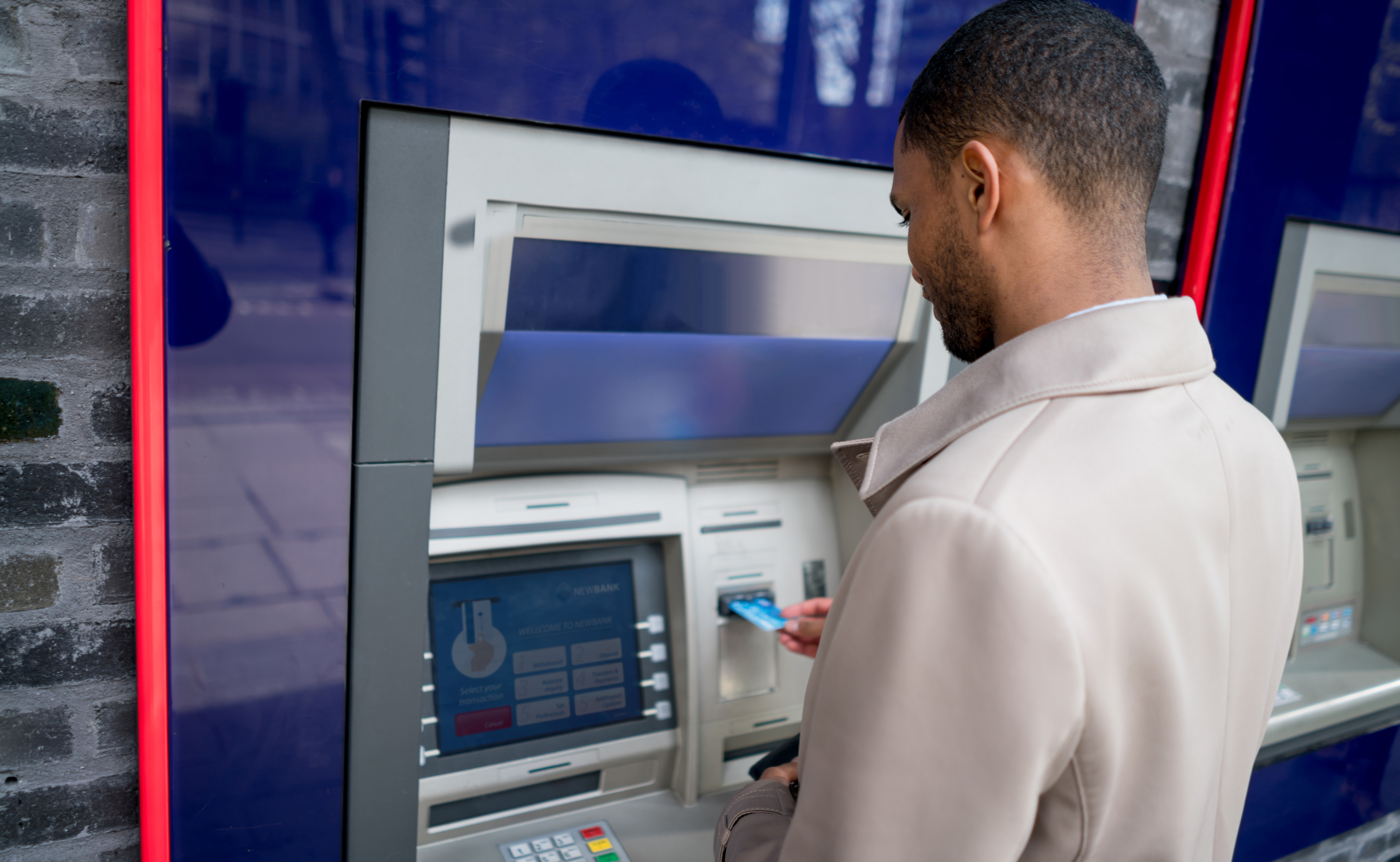 man standing in front of ATM machine