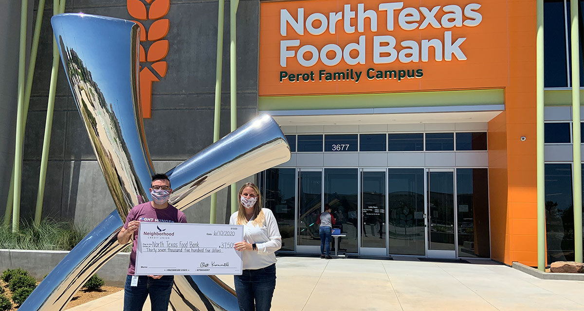 North Texas Food Bank Major Gifts Officer; Cody Meyers, and Neighborhood Credit Union VP, Marketing & Communications; Jessie Swendig. both are holding a check to the food bank in front of a silver statue.