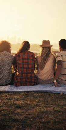 Group of friends sitting on blanket at a scenic overlook