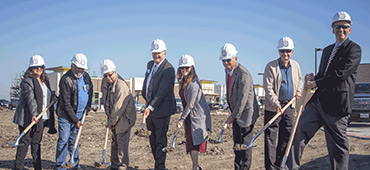 Group of people with hard hats breaking ground on new credit union location
