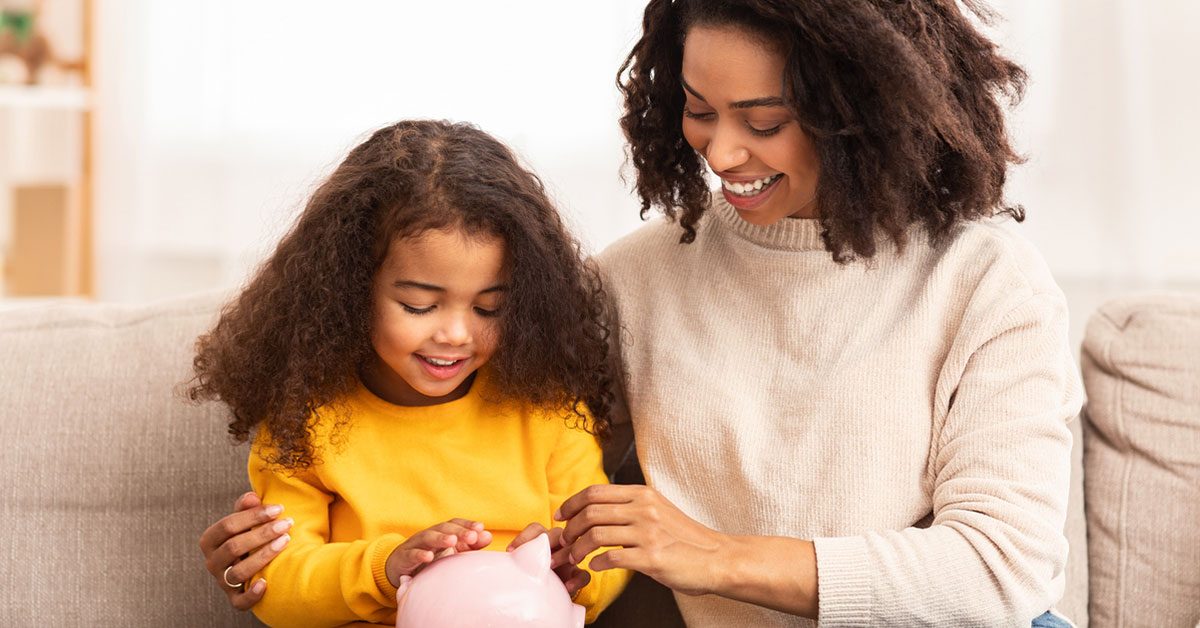Mom and daughter smiling looking at piggy bank.