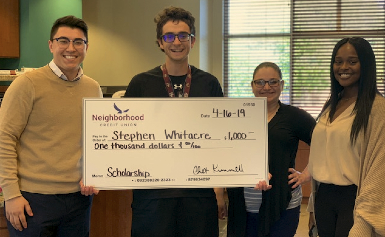 Group of people standing and smiling holding a large check