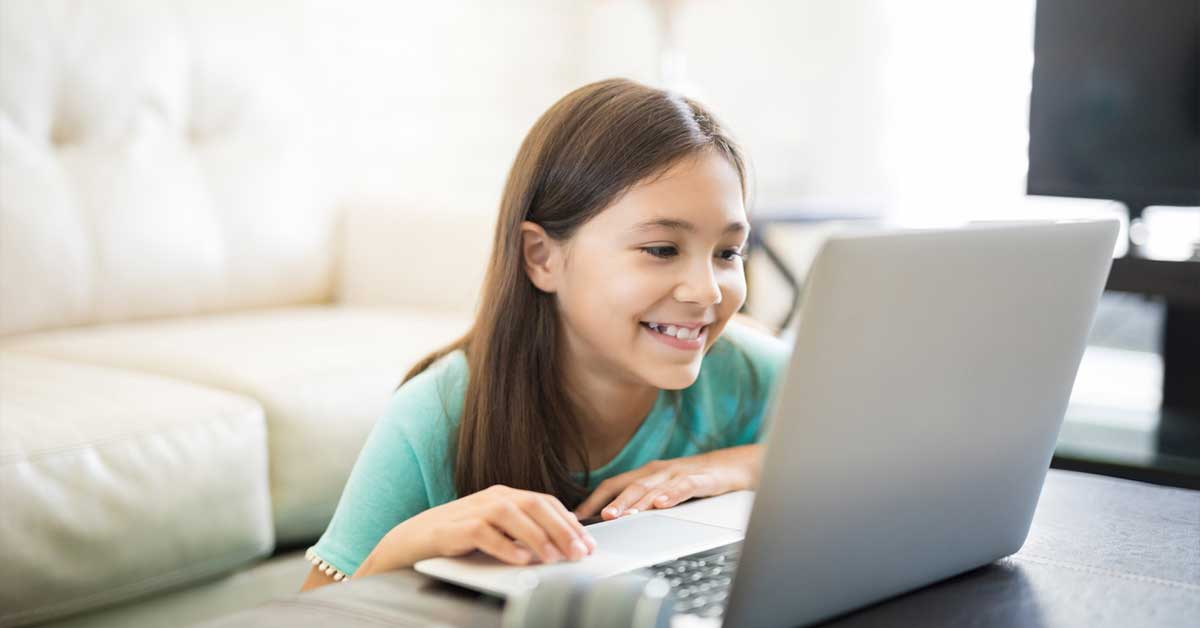 Young girl smiling and laughing at computer