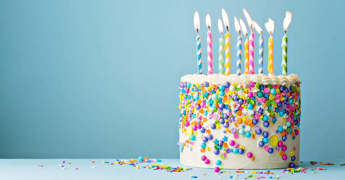 Still shot of a birthday cake with sprinkles and a blue background.