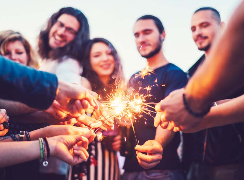 Group of friends holding sparkler fireworks