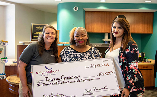 Three people standing around a big check smiling